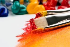 Art Supplies showing paint brushes dipped in red and orange paint
