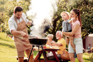 Family having a barbecue party in their garden in summer.